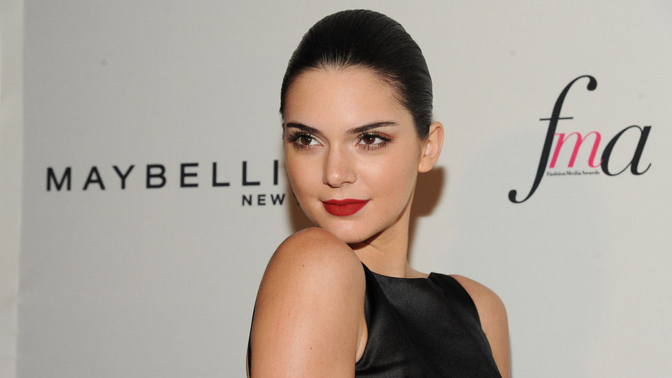 Kendall Jenner poses over her shoulder wearing black dress and red lips, Getty for Maybelline.