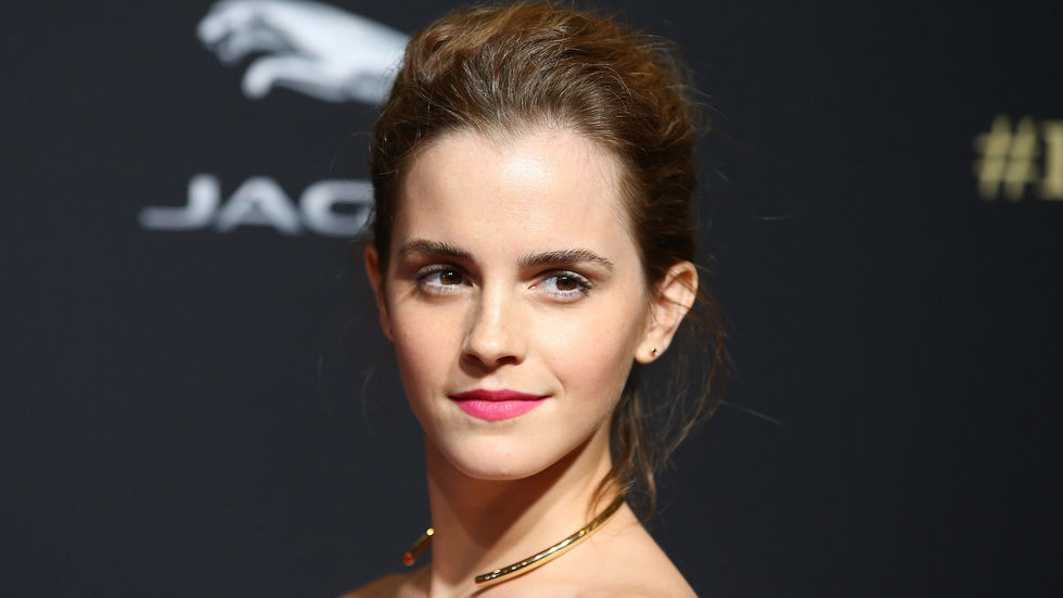 Emma Watson turns her head, rose lipstick and gold necklace. She has her hair up and a slight smile