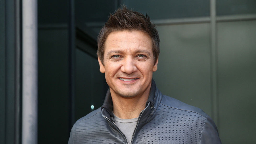 Jeremy Renner portrait smiling at camera in blue shirt