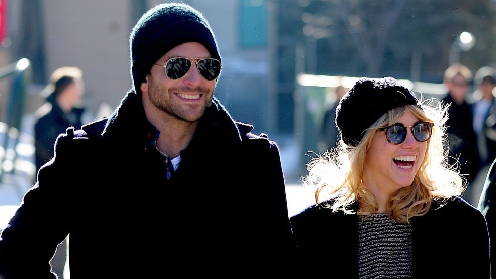 Bradley Cooper and Suki Waterhouse taking a walk in winter smiling, warm in beanies.