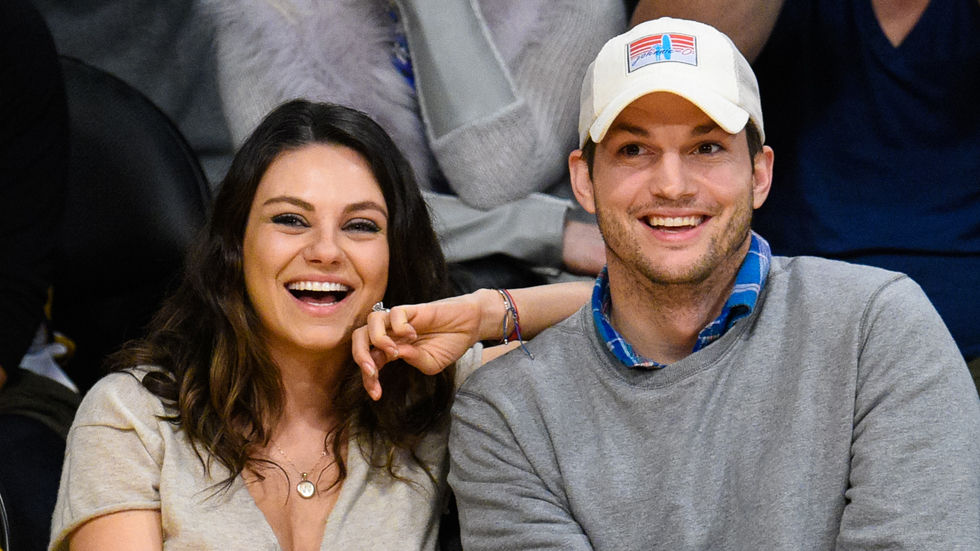 Ashton Kutcher and Mila Kunis laughing at a basketball game.