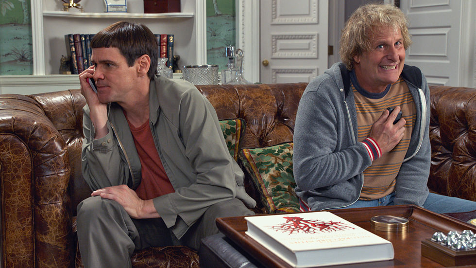 Harry and Lloyd on the couch talking to each other on their cell phone.