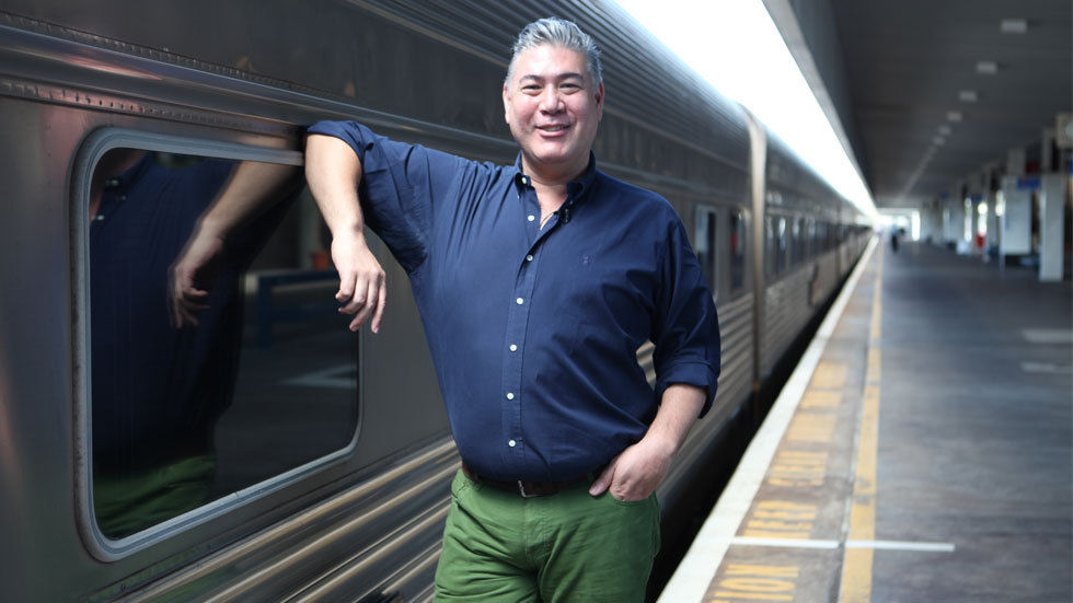 Jonathan Phang poses next to a train for Gourmet Trains on Travel Channel