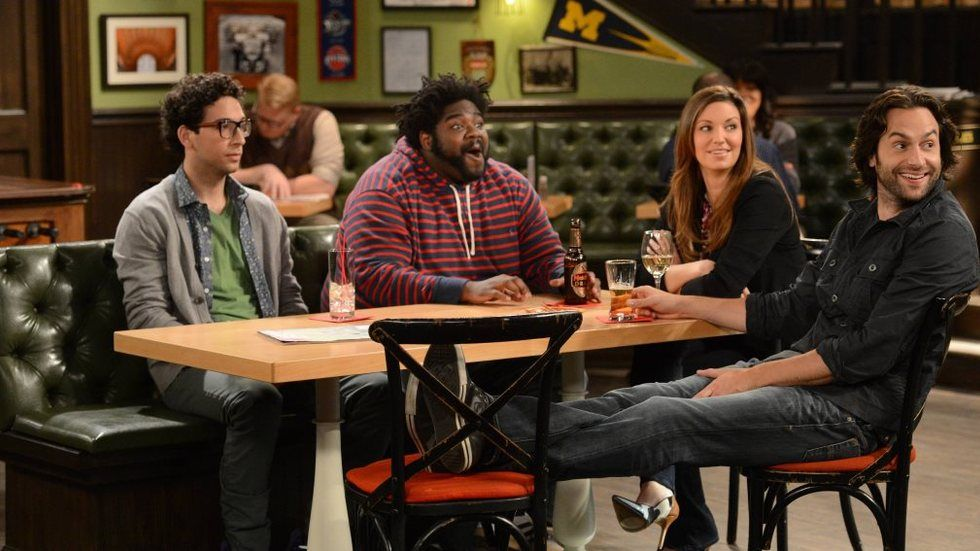 the cast of undateable on set in a bar scene all looking at something of interest.