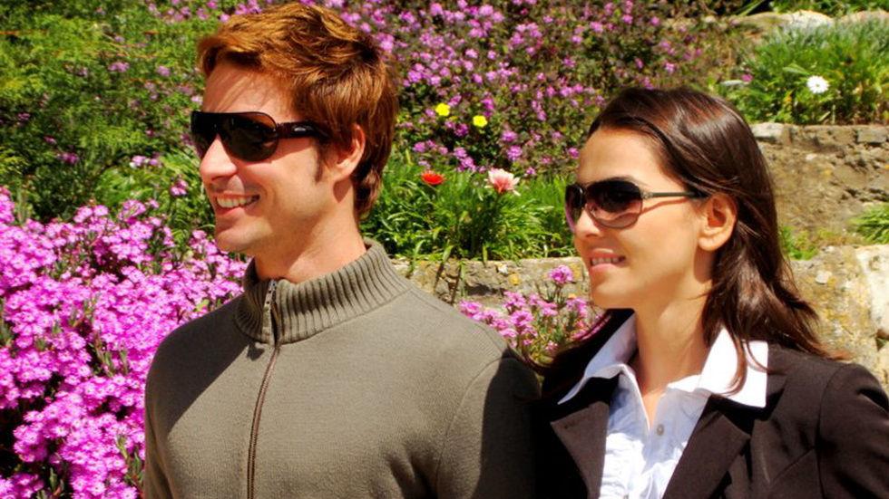 Lucas de casaco cinzento de feixo ate a gola e oculos escuros com a Victoria de camisa branca e blazer preto num jardim onde tem flores cor de rosa