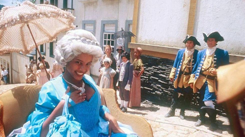 Xica a passear de carroçaria pela cidade com vestido azul e sombrinha