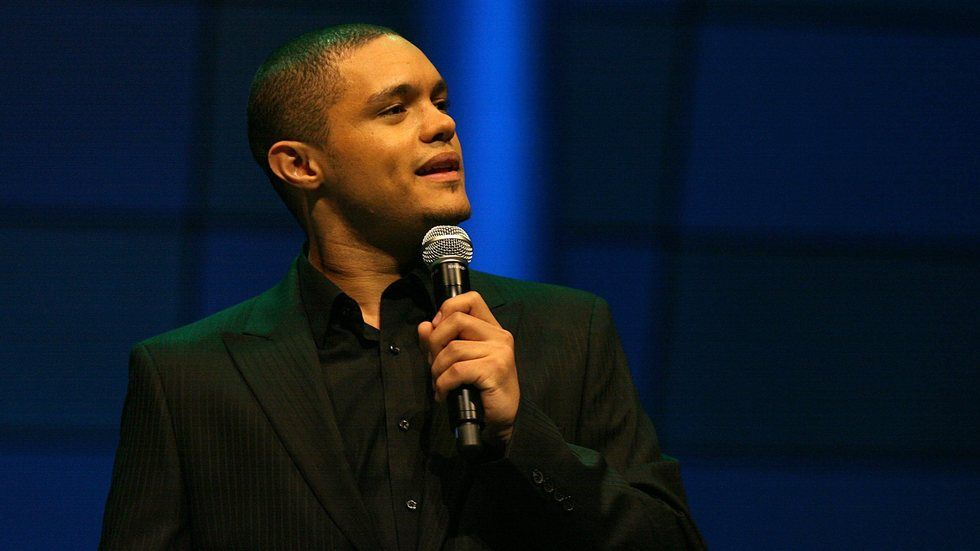 Trevor Noah holding mic on blue background