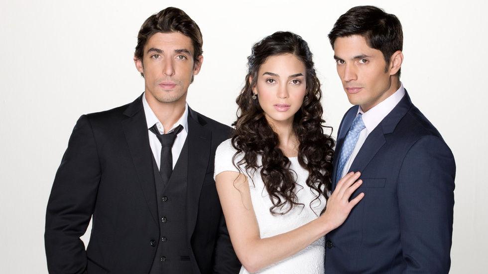 rapariga de cabelo encaracolado de vestido branco entre 2 homens de terno o a sua esquerdade terno azul e gravata azul ao qual ela esta abrazada e o outro do seu lado direito terno preto