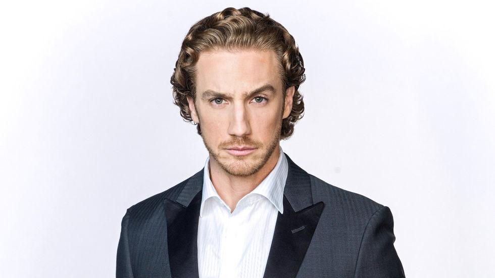 Nicolas de terno preto e camisa branca com a testa franzida