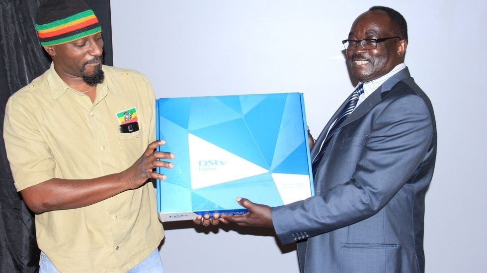 Chairman MultiChoice Uganda hands over an Explora to Gaetano Kaggwa at BoxOffice launch in Uganda.