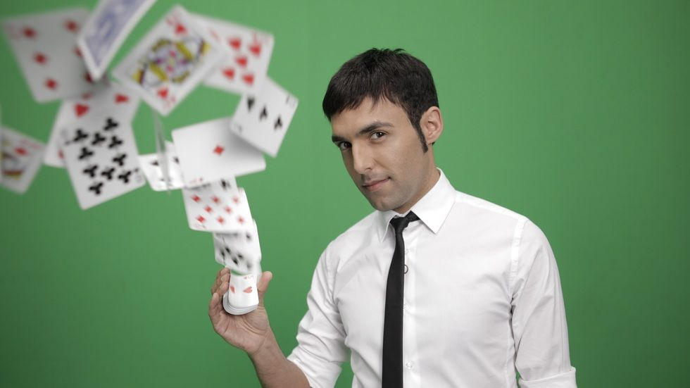 Antonio Diaz with a deck of cards with a green background.