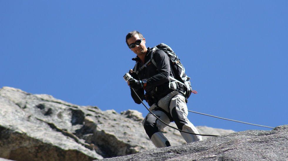 Bear Grylls climbing a mountain.
