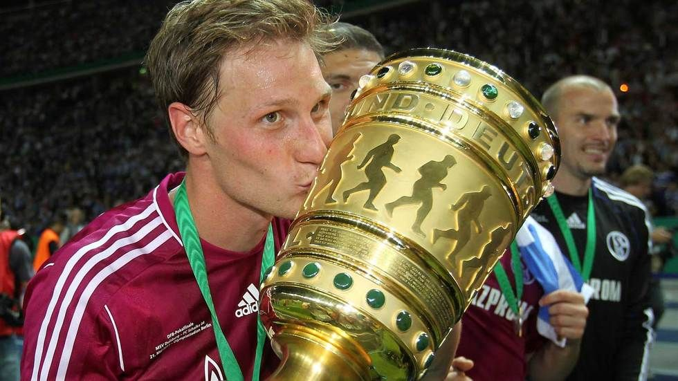 Benedikt Hoewedes kisses the German Dfb Cup at the 2011 final.