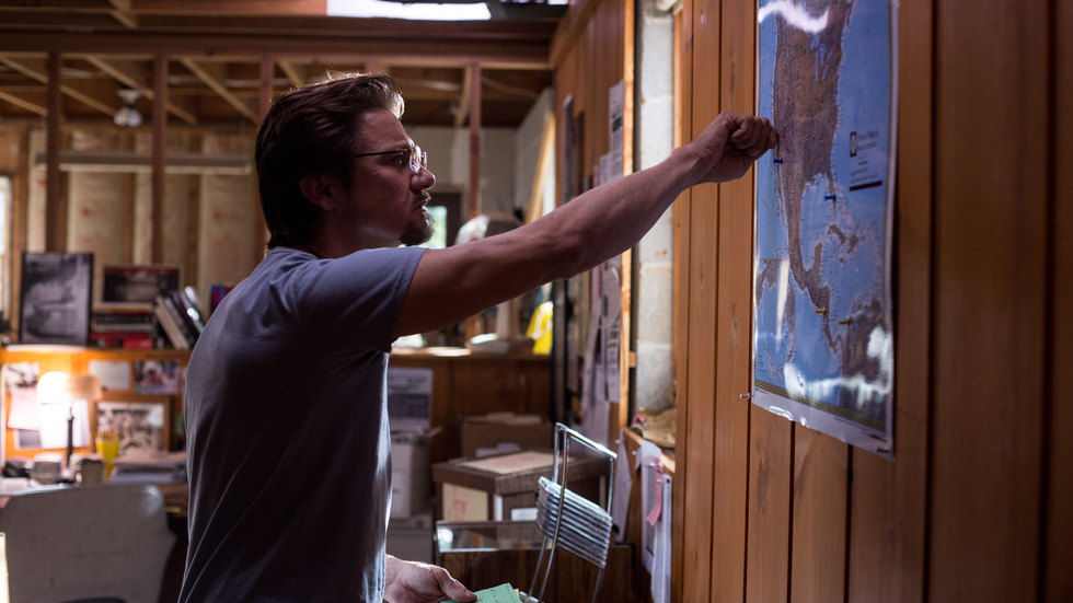 A picture of Jeremy Renner putting pins on a map in Kill the Messenger.