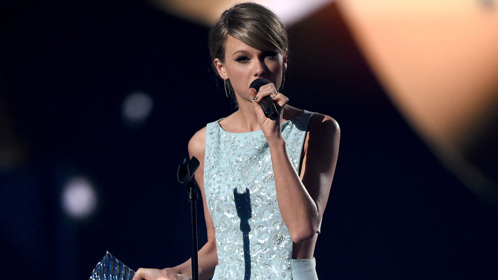 Taylor Swift wearing a blue dress and making a speech with an award in her hand at the ACM 2015 awards.
