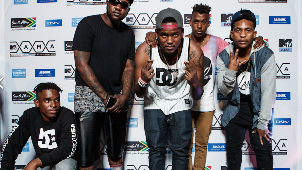 Members of a rap group pose for a photo on the MAMA 2015 red carpet.