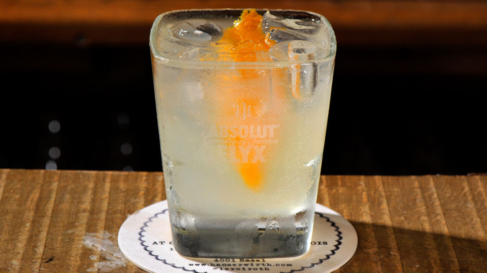 An image of a glass with an orange cocktail.