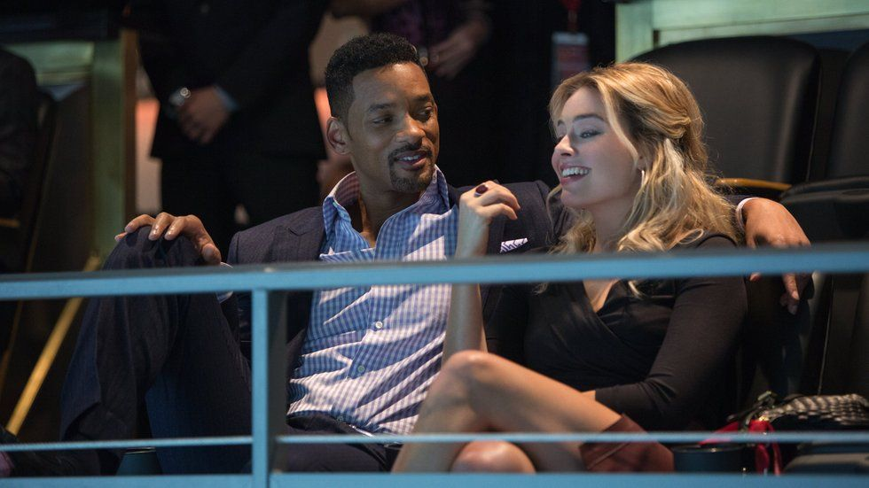 Will Smith sitting with his arm around Margot Robbie in the movie Focus.