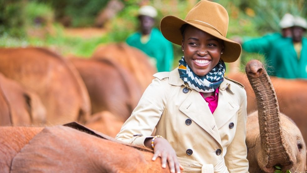 Oscar winner Lupita Nyong'o posing with elephants in Kenya.