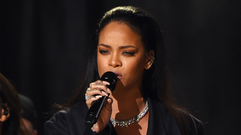 Rihanna with long black hair sleeked back, holding a microphone.