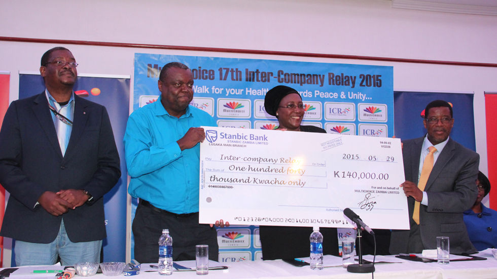 Former MultiChoice Zambia General Manager Simon Bota presents a cheque