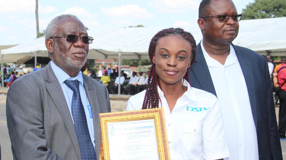 Zambia's Minister of Labour, Honorable Fackson Shamenda presents a long service award to MultiChoice Zambia's Joan