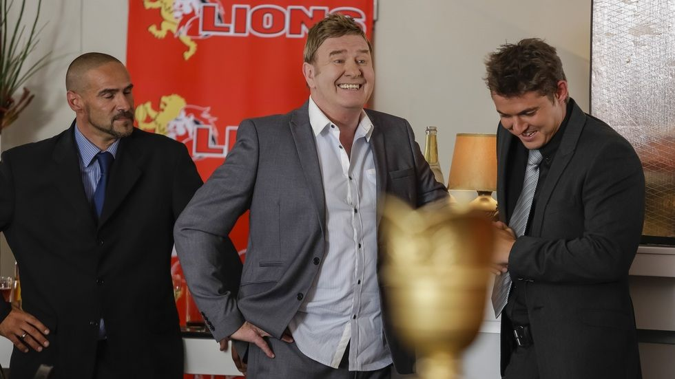 Leon Schuster from Shucks! Pay Back the Money! With Lion Cup and Lions Banner.