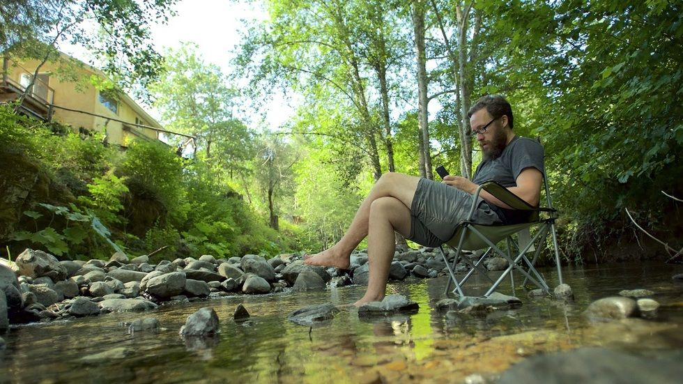 Evan Henshaw relaxes in a stream by a cabin in the woods.