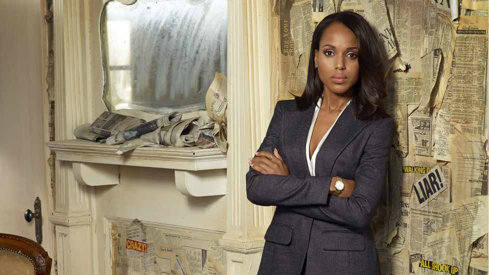 Kerry Washington as Olivia Pope leans against a newspaper-covered wall.