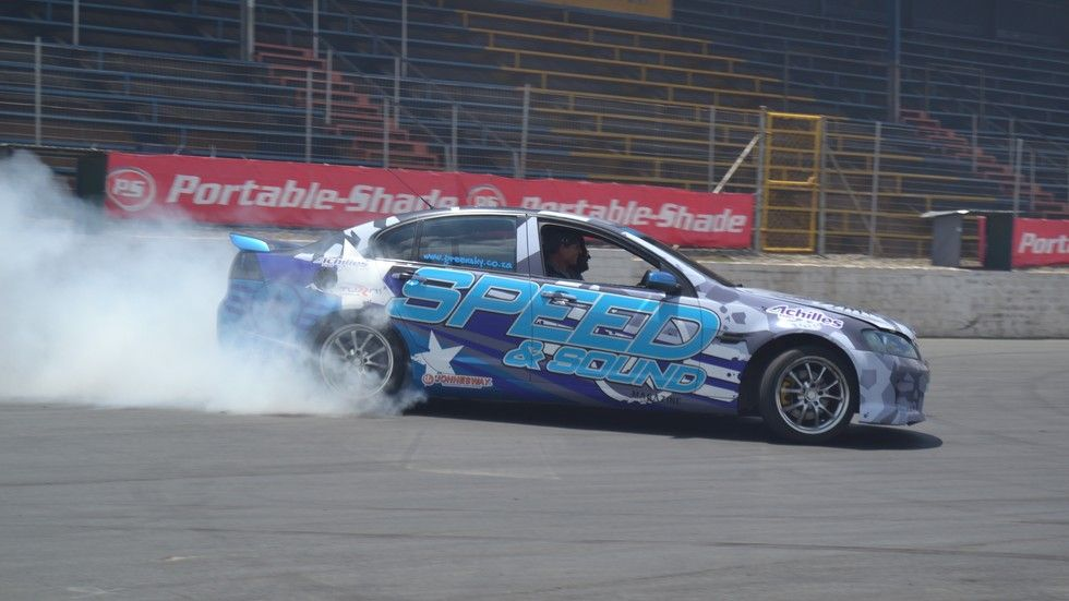 """An image of a car that is """"drifting""""."""