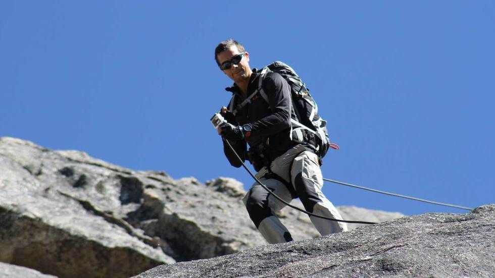 Bear Grylls goes down a mountain slope.
