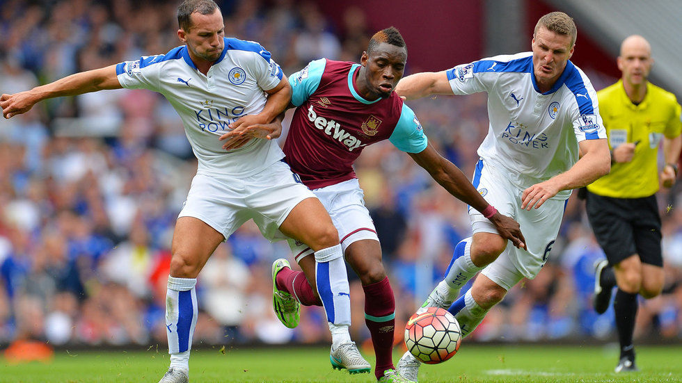 Diafra Sakho of West Ham United is challenged by Danny Drinkwater and Robert Huth of Leicester City