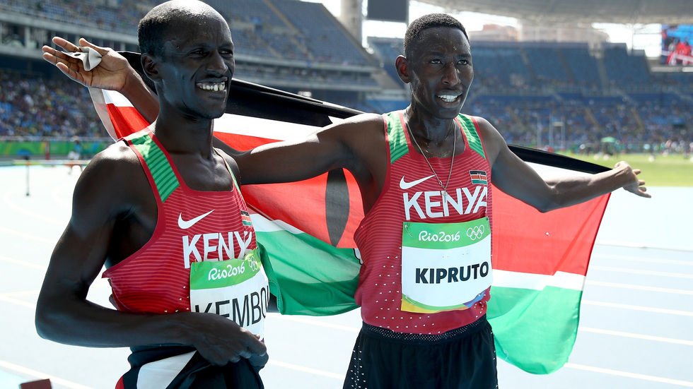 Kipruto and Kemboi pose with the Kenyan flag