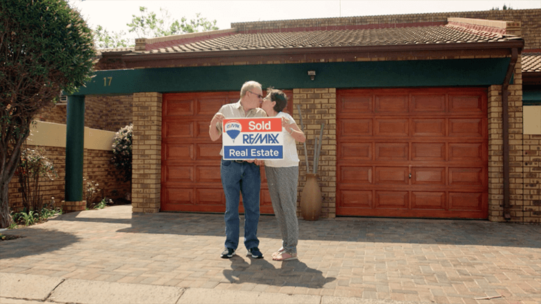 Bela and Paddy Abrahams in front of garage holding REMAX sign.