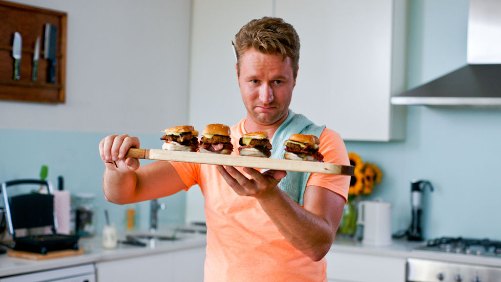 Man carrying four burgers.