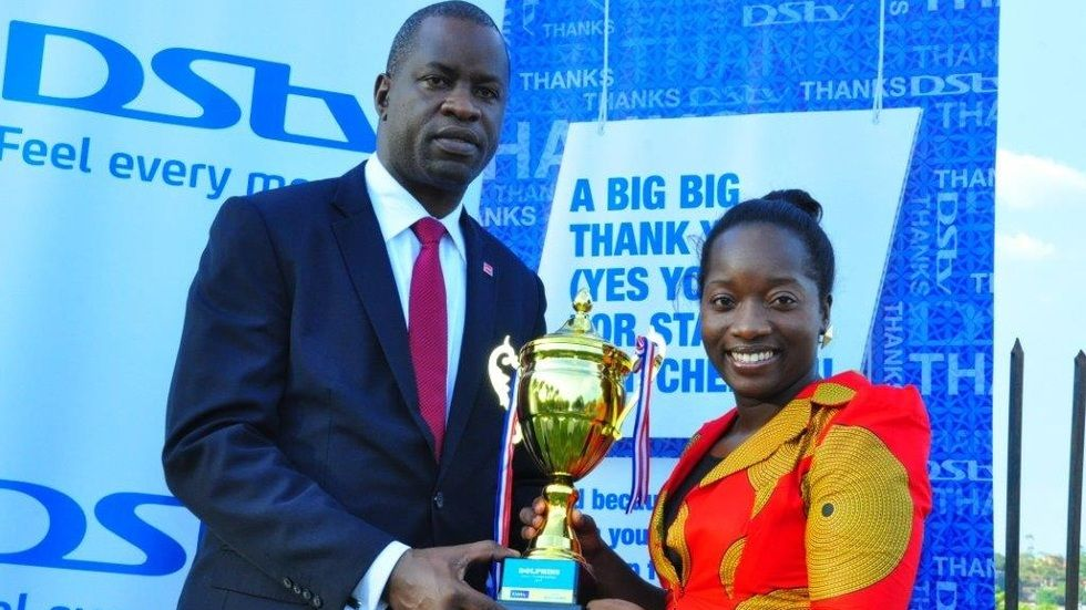 Tina Wamala (R) PR Manager  MultiChoice Uganda hands over trophy sponsorship package to Sam Ntulume Chairman of Dolphins Swimming Club for their gala this weekend