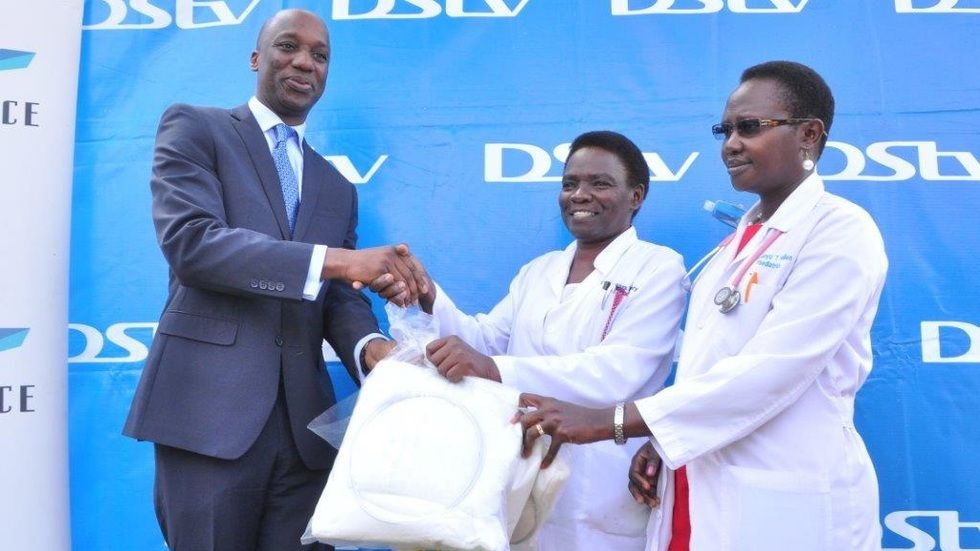 Charles Hamya (L) GM MultiChoice Uganda hands over a sample of mosquito nets to Dr Nassanga (c) Deputy ED Mulago Hospital and Dr Aanyu Hellen head of the acute ward.