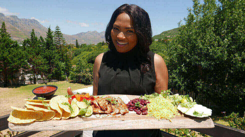 Siba Mtongana poses with a tray of taco ingredients on her show Siba's Table.
