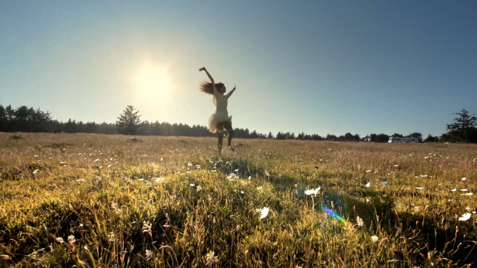 A women jumping for joy in a sunny field.