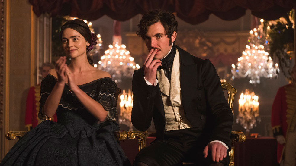 Victoria and Prince Albert sit together, she applauds, chandeliers in the background