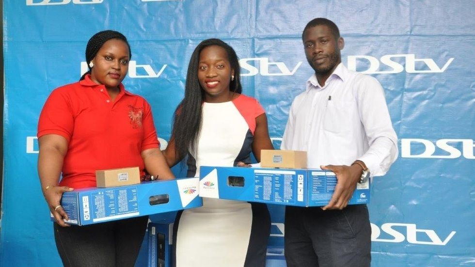 Tina Wamala (C) PR Manager poses with Arinda Athia and Ojur Marcellino, DStv customers who won Explora decoders in the We are the Premier League campaign.