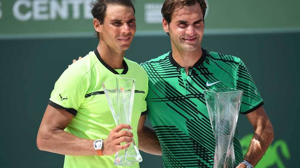 Nadal and Federer arm in arm holding trophies.