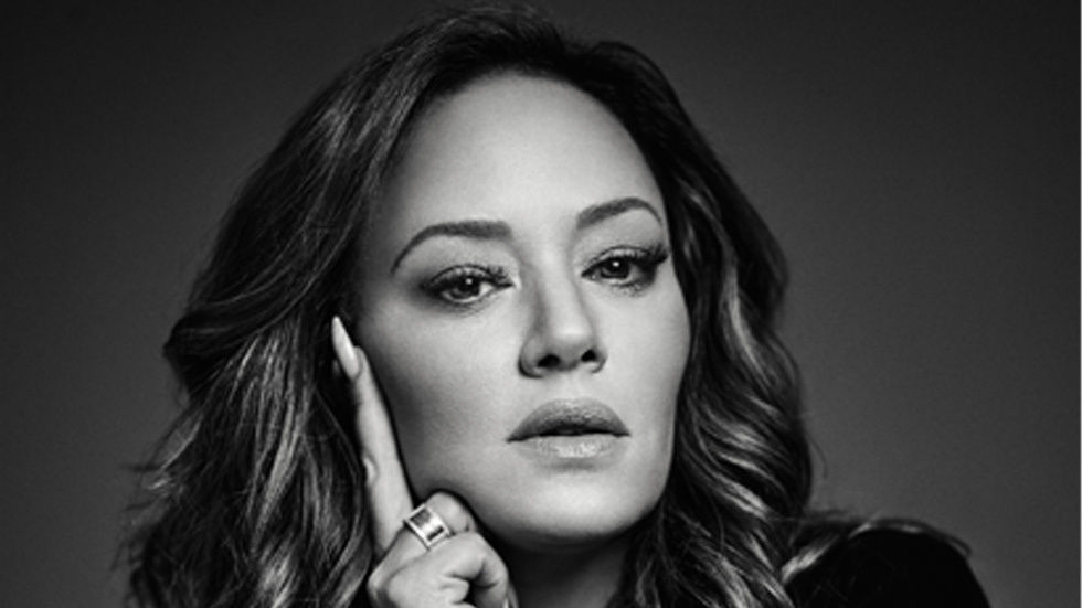 Leah Remini with her hand on her face.