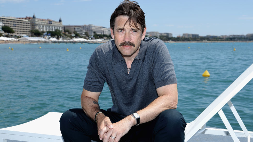 Dougray Scott sits in a boat.
