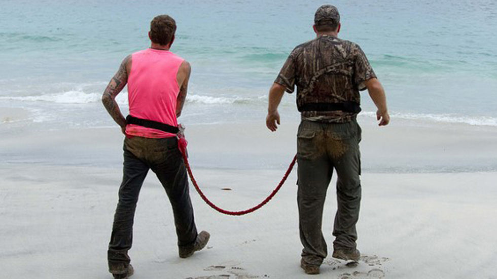 2 men walk on beach tied together with a rope
