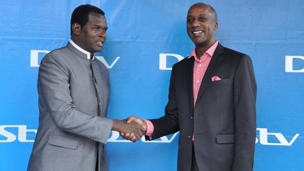Charles Hamya, General Manager MultiChoice Uganda shakes hands with Pastor Robert Kayanja at the launch of Channel 44 on DStv platform