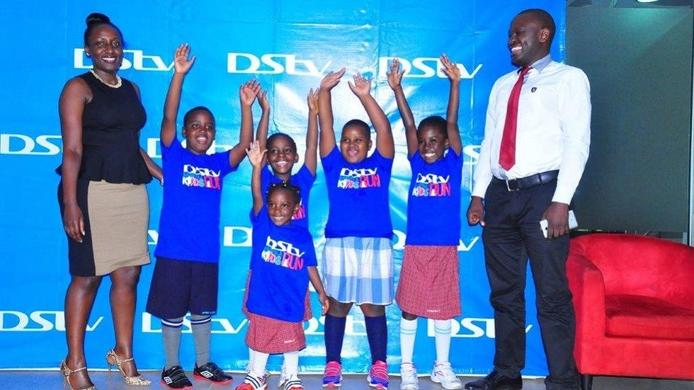 Phoebe Nakabazzi (L) DStv Marketing Manager and Muslin Kiwanuka (R) Chairman of Kampala Kids run pose with excited children who will partake in this years DStv Kampala Kids Run.JPG