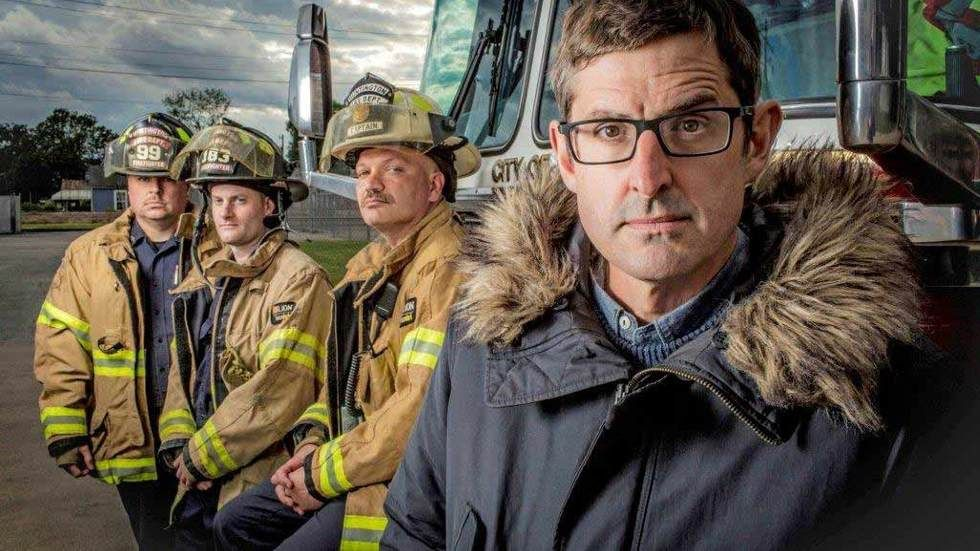Louis Theroux stands with firefighters