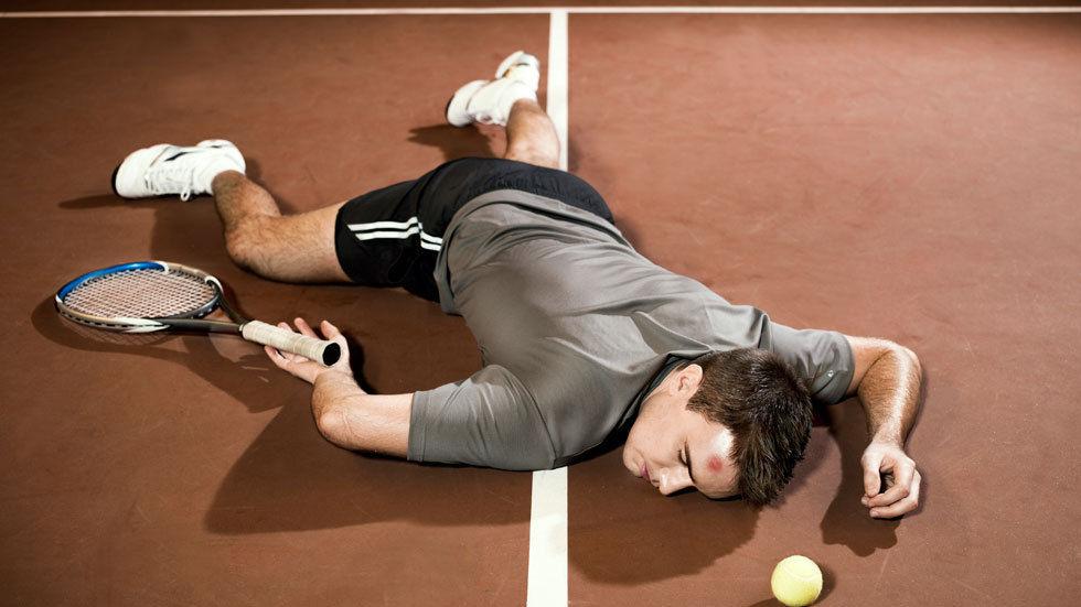 An injured tennis player lies on the court