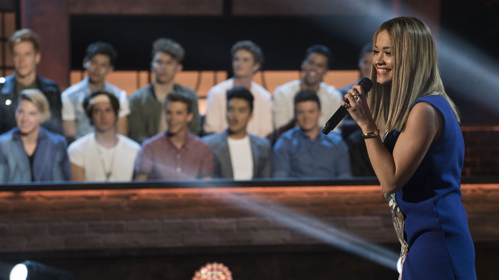 A scene from Boy Band S1 with RIta Ora and the contestants in the background.